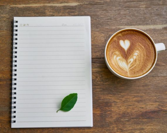 coffee cup & notebook with green leaf